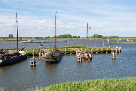 Barge on river Boven-Merwede and sailboats in historic harbour of old fortified town of Woudrichem, Brabant, Netherlands Stock Photo