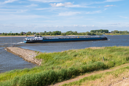 Binnentank, schip, scheeps, stroomopwaarts, op, rivier, Waal, en, vissende, man, op, golfbreker, op, zuidoever, dichtbij, Zuilichem, Bommelerwaard, Gelderland, nederland