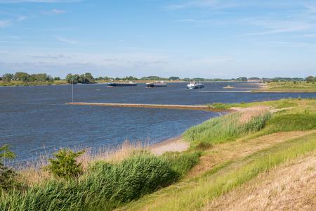 Panorama van rivier de Waal met kribben en binnenvaartvaart vanaf dijk op zuidoever bij Zuilichem, Bommelerwaard, Gelderland, Nederland Stockfoto
