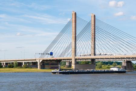 Binnenland tanker stroomafwaarts op de Waalrivier en Martinus Nijhoffbrug, Zaltbommel, Gelderland, Nederland Stockfoto
