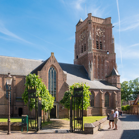 en: WOUDRICHEM, NETHERLANDS - JUN 4, 2017: Street scene with people and Saint Martins Church in centre of fortified town of Woudrichem, Brabant, Netherlands