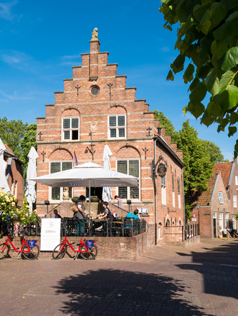 WOUDRICHEM, NETHERLANDS - JUN 4, 2017: People enjoying on outdoor terrace of cafe in old town hall in centre of fortified city of Woudrichem, Brabant, Netherlands