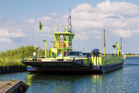 TIENGEMETEN, NETHERLANDS - MAY 20, 2017: Ferry boat with cars and passengers arriving on Tiengemeten island in Haringvliet estuary, South Holland, Netherlands