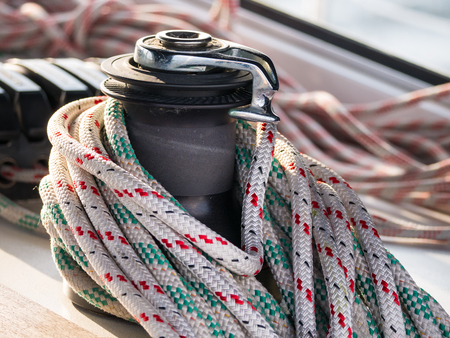coiled rope: Self-tailing winch on sailing boat with coiled rope Stock Photo