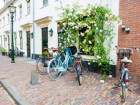 Straatscène met geparkeerde fietsen en muur van huis met beklimmende roos in oude stad van Wijk bij Duurstede in provincie Utrecht, Nederland Stockfoto - 81463497
