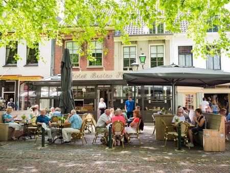 WIJK BIJ DUURSTEDE, NEDERLAND - 11 juni 2017: Mensen ontspannen op buitenterras van café op marktplein in de oude binnenstad van Wijk bij Duurstede in provincie Utrecht, Nederland Stockfoto - 81825716