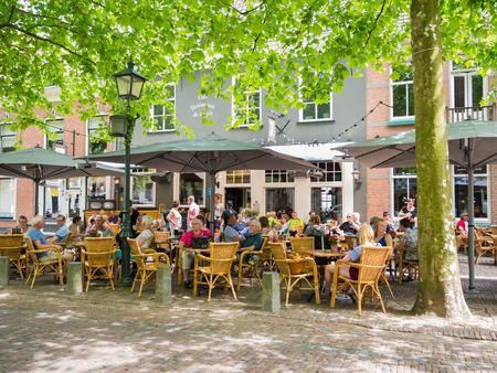 WIJK BIJ DUURSTEDE, NEDERLAND - 11 juni 2017: Mensen ontspannen op buitenterras van café op marktplein in de oude binnenstad van Wijk bij Duurstede in provincie Utrecht, Nederland Stockfoto - 81825717