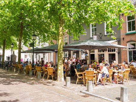 WIJK BIJ DUURSTEDE, NETHERLANDS - JUN 11, 2017: People relaxing on outdoor terrace of cafe on market square in old town of Wijk bij Duurstede in province Utrecht, Netherlands