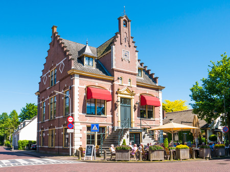 LAREN, NETHERLANDS - MAY 25, 2017: People relaxing on outdoor terrace of restaurant in former town hall of Laren, North Holland Editorial