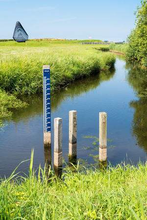 depth gauge: Water level staff gauge in ditch in polder Schokland, Noordoostpolder, Flevoland, Netherlands