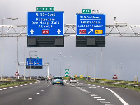 Traffic on motorway A4 and overhead route information signs, The Hague, South Holland, Netherlands