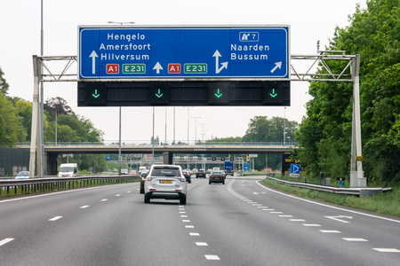 Traffic on motorway A1 and overhead route information signs, Naarden, North Holland, Netherlands