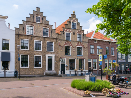 OUD-BEIJERLAND, NETHERLANDS - MAY 21, 2017: Street scene of Havendam with front facade of historic houses with stepped gables in old town of Oud-Beijerland, Hoeksche Waard, South Holland, Netherlands