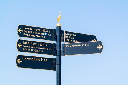 Signpost with tourist information signs on waterfront promenade in Scheveningen, The Hague, Netherlands