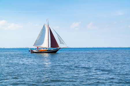 People on traditional flatbottom sailboat sailing on Waddensea near island Texel, Netherlands on a sunny summer day