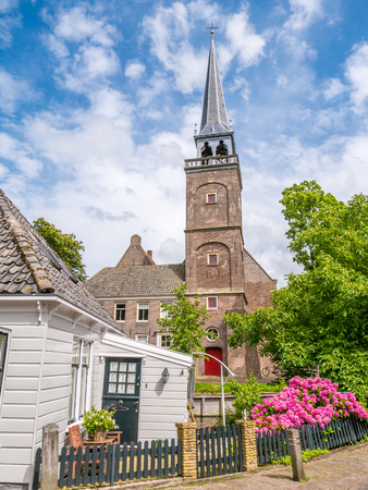 Street scene with church tower and part of wooden house in historic old town of Broek in Waterland, Noord-Holland, Netherlands