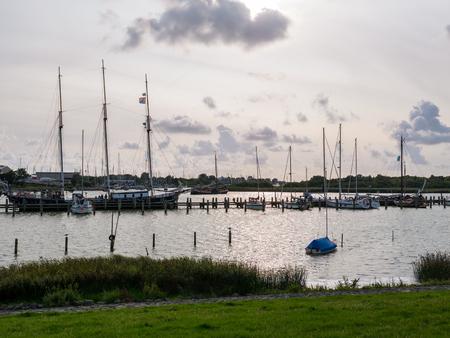 Boats moored at jetties in marina Makkumerdiep in old town of Makkum, Friesland, Netherlands