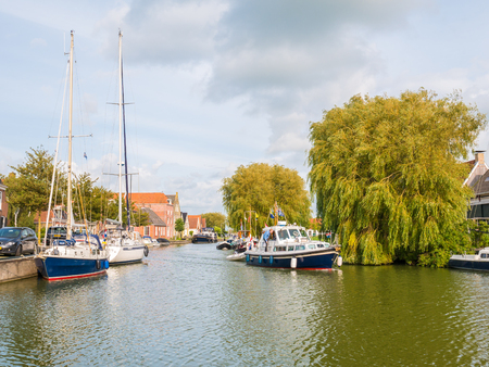 People on boat sailing on canal in harbour of old town of Makkum, Friesland, Netherlands