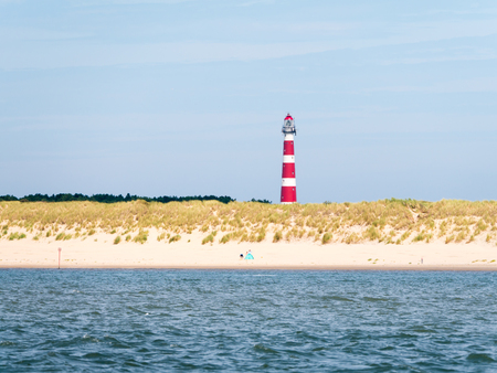 Beach and lighthouse of Ameland island in Wadden Sea, Friesland, Netherlands
