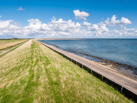 Dike with grass protecting polders on West Frisian island Texel against Wadden Sea, Netherlands Stockfoto - 114264822