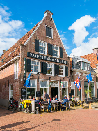 People enjoying drinks and snacks at outdoor terrace of cafe in historic old town of Dokkum, Friesland, Netherlands