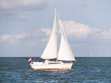 People on sailboat sailing on lake IJsselmeer and wind turbines of wind farm Urk, Netherlands