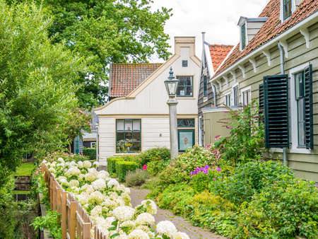 Wooden house and garden with plants and flowers in picturesque old town of Broek in Waterland, Noord-Holland, Netherlands
