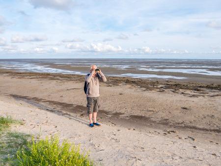 Senior man with binoculars on beach of nature reserve Boschplaat on island Terschelling, Netherlands at low tide of Wadden Sea Stock Photo
