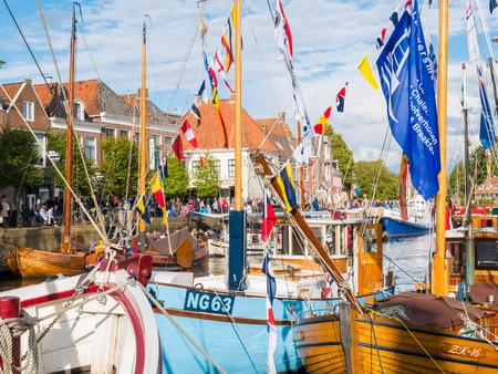 People and decorated boats in harbour during event Admiralty Days of Dokkum in Friesland, Netherlands