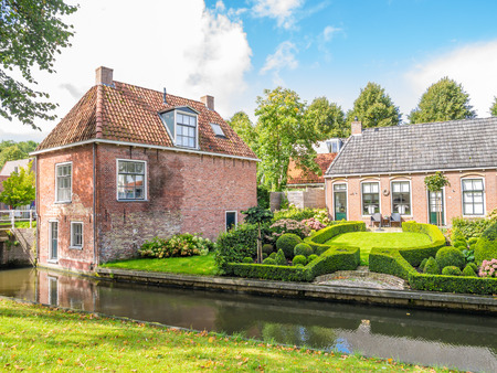 Street scene of Oranjewal canal with waterfront houses and gardens in old town of Dokkum, Friesland, Netherlands Editorial