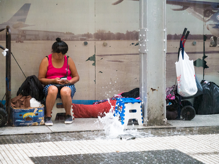 Vendor hiding for heavy rain storm in pedestrian zone of city centre Microcentro, Monserrat district in capital Buenos Aires, Argentina Editorial