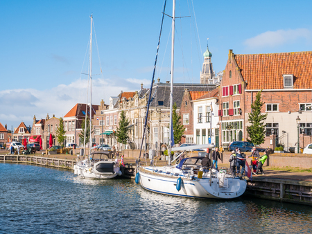 People and sailboats on canal in old town of Enkhuizen, North Holland, Netherlands Editorial