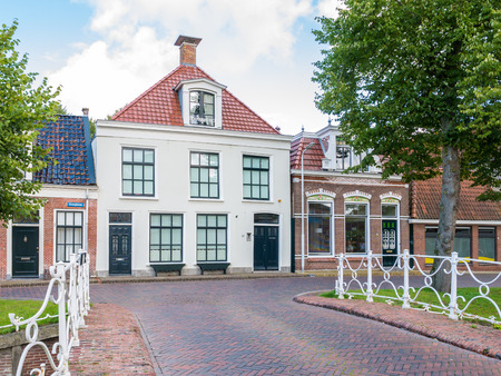 Oranjewal canal with waterfront house and bridge in old town of Dokkum, Friesland, Netherlands Editorial