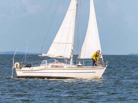 Man on foredeck of sailboat sailing on lake IJsselmeer near Enkhuizen, Netherlands