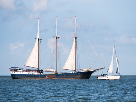 Authentic sailing ship, schooner, sailing very close to small sailboat on lake IJsselmeer, Netherlands