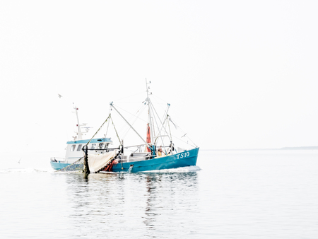 High key image of shrimp fishing trawler off coast Vlieland on Wadden sea, Netherlands