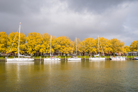 Autumn trees and sailing boats in old harbour of city of Enkhuizen, Noord-Holland, Netherlands