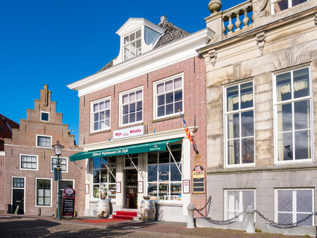 Front facades of historic houses and liquor store on Dijk quay in harbour of old town of Enkhuizen, Noord-Holland, Netherlands Editorial