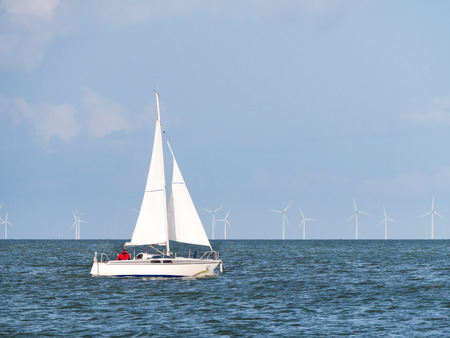 People on sailboat sailing on lake IJsselmeer and wind turbines of wind farm Urk, Netherlands