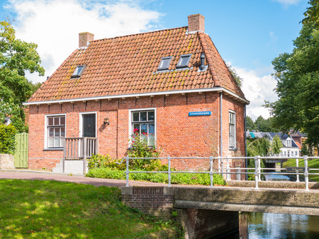 DOKKUM, NETHERLANDS - SEP 12, 2017: Oranjewal canal with waterfront house and bridge in old town of Dokkum, Friesland, Netherlands