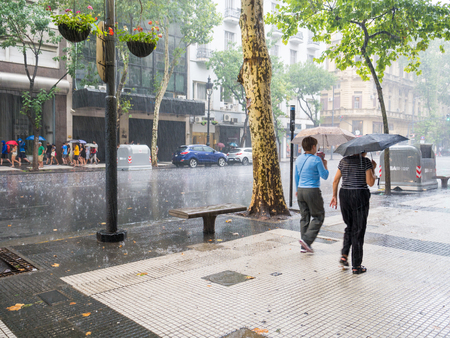 People walking with umbrellas in heavy rain storm on Avenida de Mayo in city centre Microcentro, Monserrat district in capital Buenos Aires, Argentina