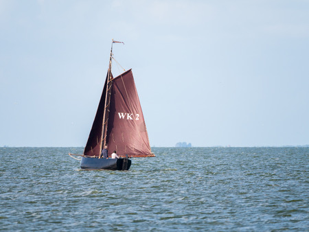 People on authentic sailboat with brown sails sailing on lake IJsselmeer near Enkhuizen, Netherlands
