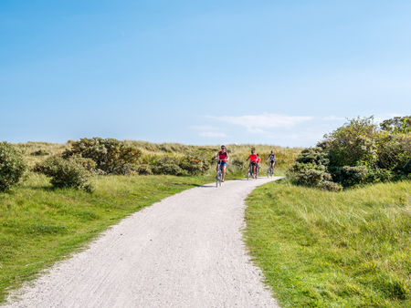People riding bicycles on bicycle path in dunes of nature reserve Het Oerd on West Frisian island Ameland, Friesland, Netherlands Editorial