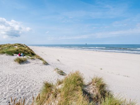 People sitting together on sand dune looking over beach and North Sea on West Frisian island Ameland, Friesland, Netherlands