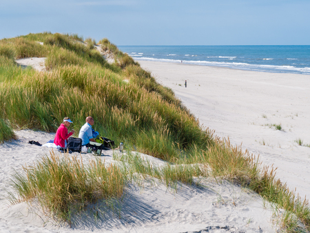 People having picnic on sand dune looking over beach and North Sea on West Frisian island Ameland, Friesland, Netherlands