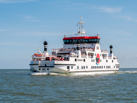 Car ferry boat with passengers sailing on Wadden Sea from West Frisian island Ameland to Holwerd in Friesland, Netherlands