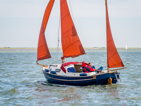 People sailing on sailboat on Wadden Sea near coast of West Frisian island Ameland, Friesland, Netherlands Editorial