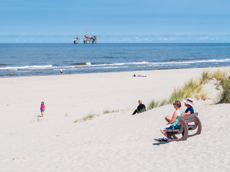People on beach and North Sea with offshore drilling platform, West Frisian island Ameland, Friesland, Netherlands