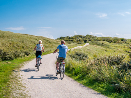 Rear view of people riding bicycles on bicycle path in dunes of nature reserve Het Oerd on West Frisian island Ameland, Friesland, Netherlands