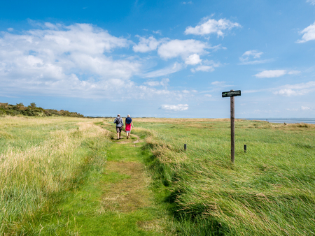 People walking on footpath and no access sign in nature reserve Het Oerd at Wadden Sea coast of West Frisian island Ameland, Friesland, Netherlands